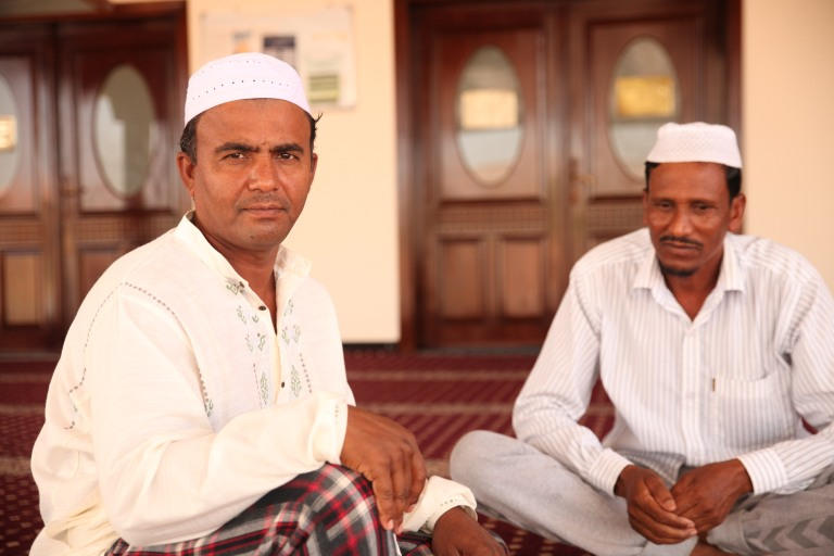 Two men talking outside a mosque in Barsha